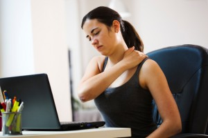 Female working at her desk with neck/shoulder pain